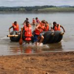 Children smiling next to raft out of water